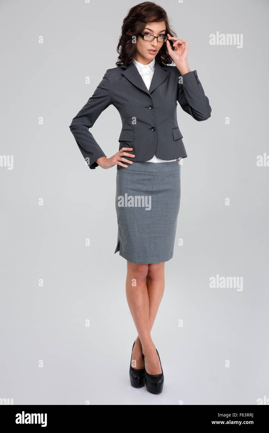 Concentrated confident curly pretty business woman in glasses and gray suit standing crossing legs and touching - Stock Image