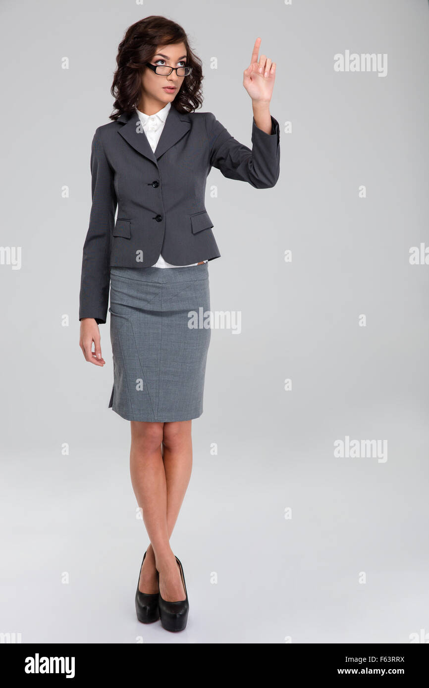 Confident curly pretty business woman in glasses and gray suit touching copyspace by finger and standing with crossed - Stock Image