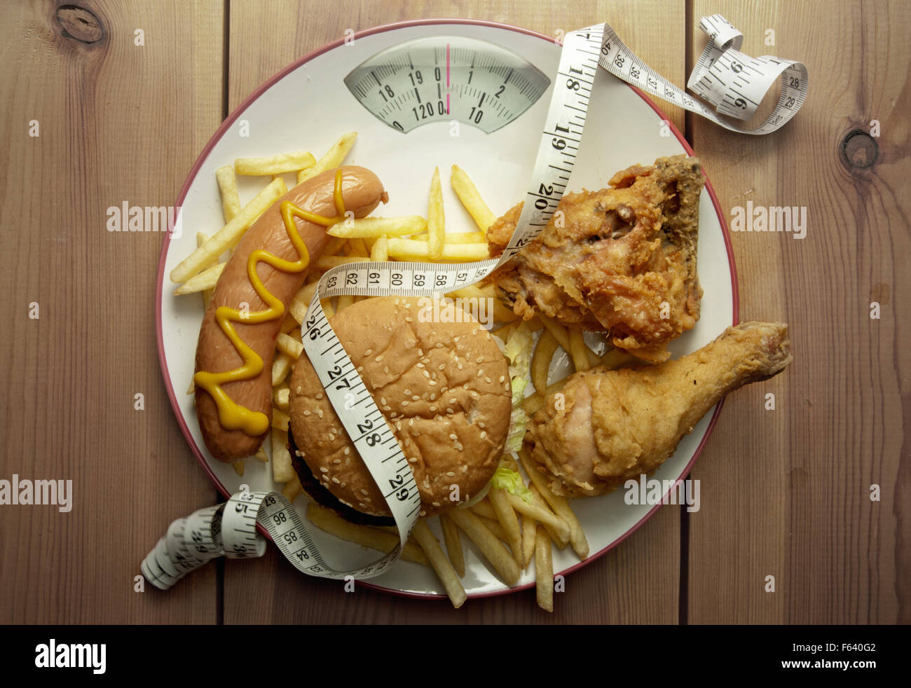 Plate packed with junk food with weighing scales - Stock Image