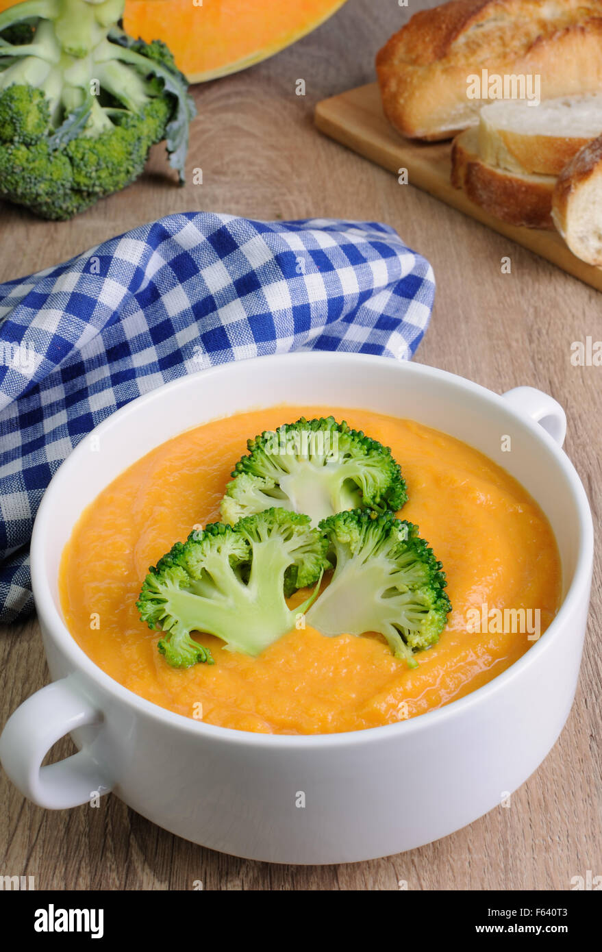 Pumpkin soup puree with cream in a dish with broccoli - Stock Image