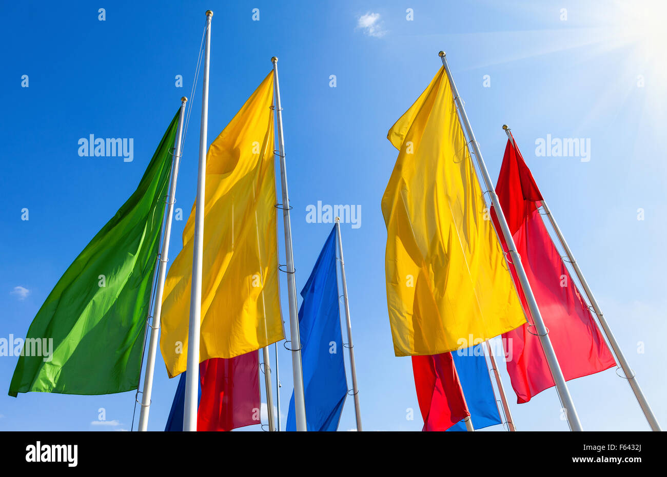Colorful flags fluttering on the blue sky background - Stock Image