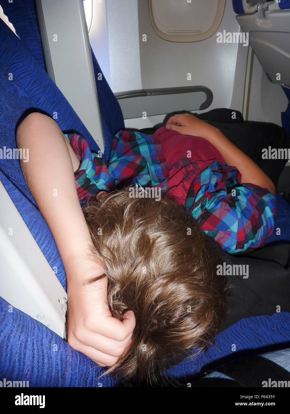 young boy sleeping on a long haul flight - Stock Image