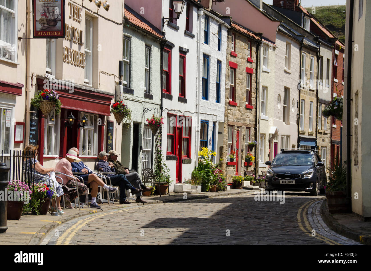 Car rounds the corner as people sit in the sun, relaxing outside pub - narrow cobbled High Street, quaint village of Staithes, North Yorkshire, UK. Stock Photo