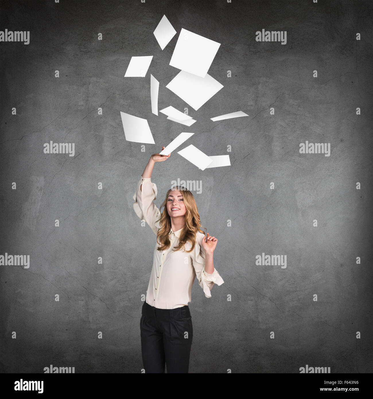 Young business woman throws up paper sheets. - Stock Image