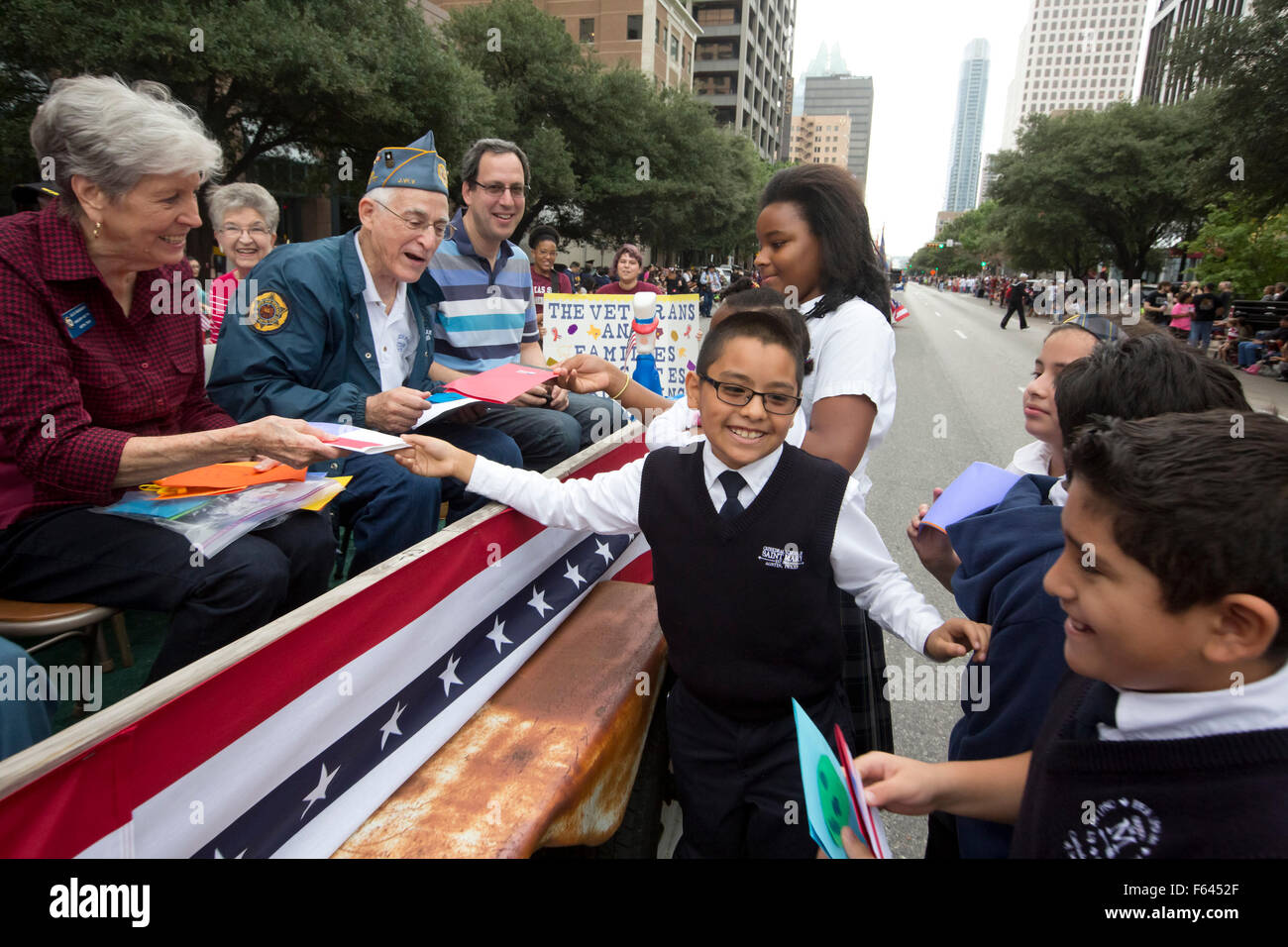 Elementary school aged children give out hand-made cards to military veterans during the Veteran's Day parade - Stock Image