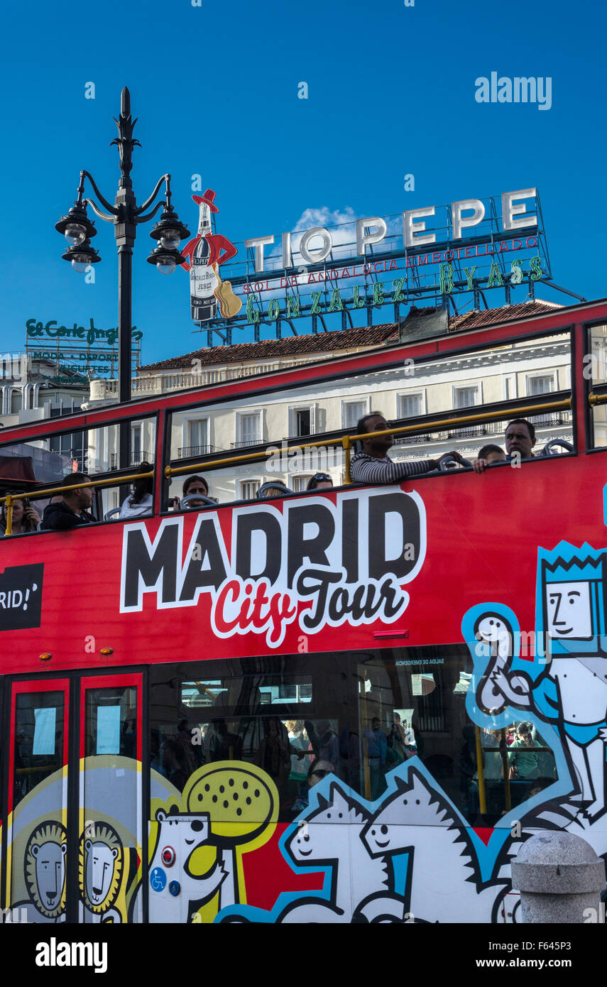 A Madrid city tour bus passes below the Tio Pepe advertising sign  in the Puerta del Sol,  Madrid, Spain. - Stock Image