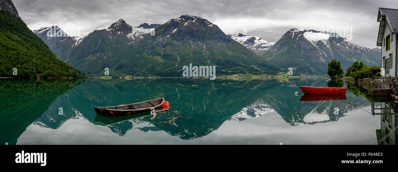 Panorama of two old rowboats  with reflection of the mountains in the still water of Oppstrynsvatnet lake in a Norway - Stock Image