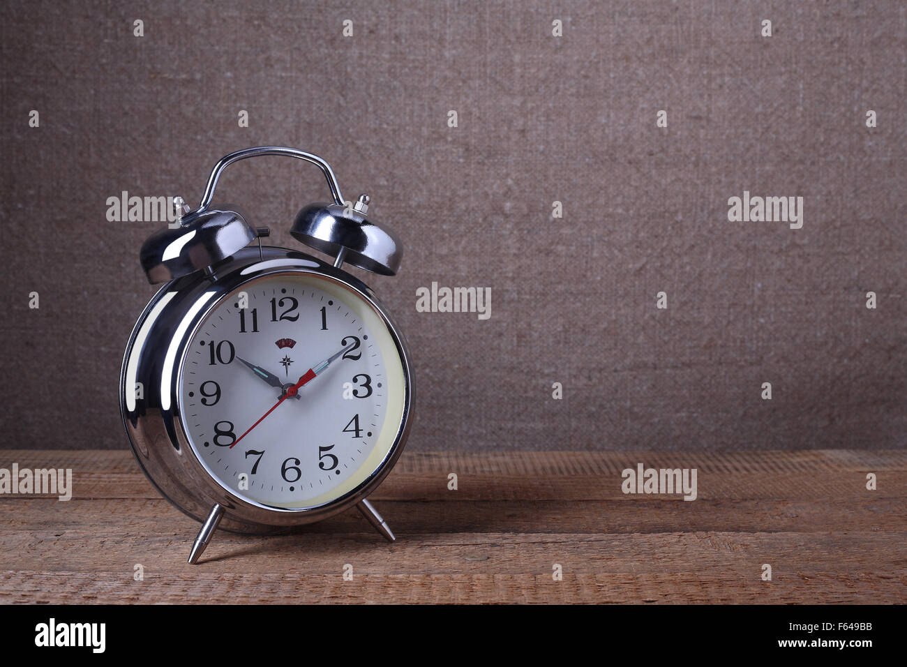 Vintage old alarm clock on sackings and a wooden background. Stock Photo