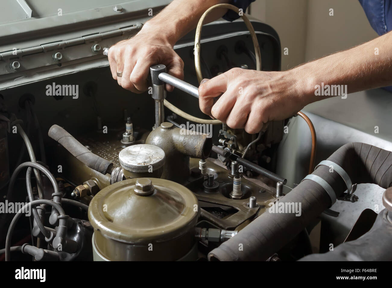 Auto mechanic working under the hood of an old car engine. Stock Photo