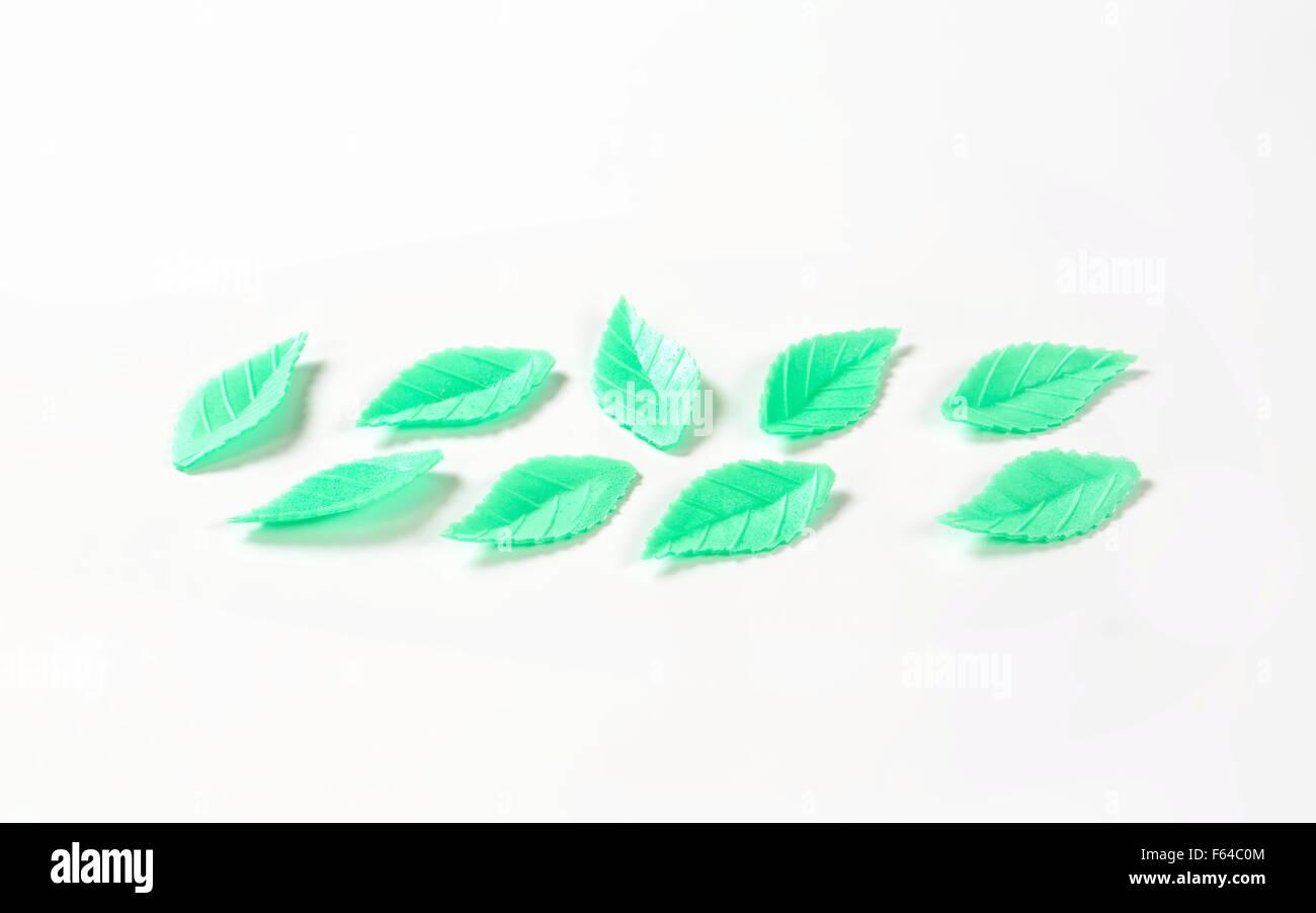 green sugar leaves - eatable cake decoration on white background - Stock Image