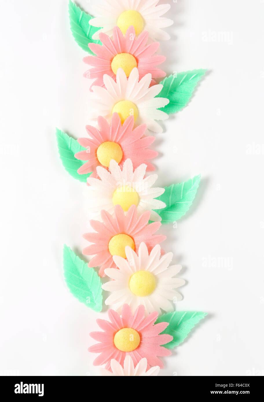 sugar flowers - eatable cake decoration on white background - Stock Image