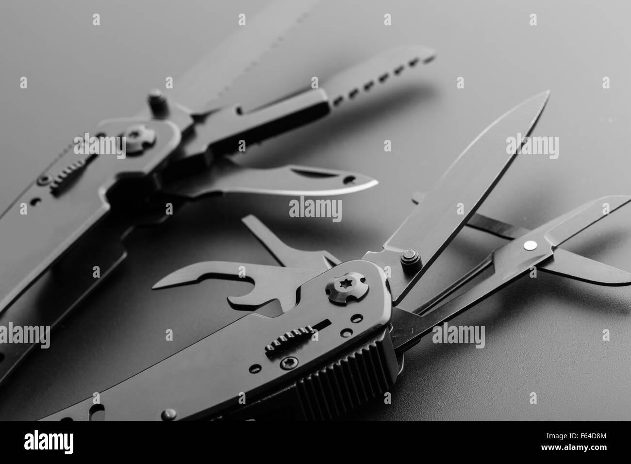 Black opened multitool knife closeup - Stock Image