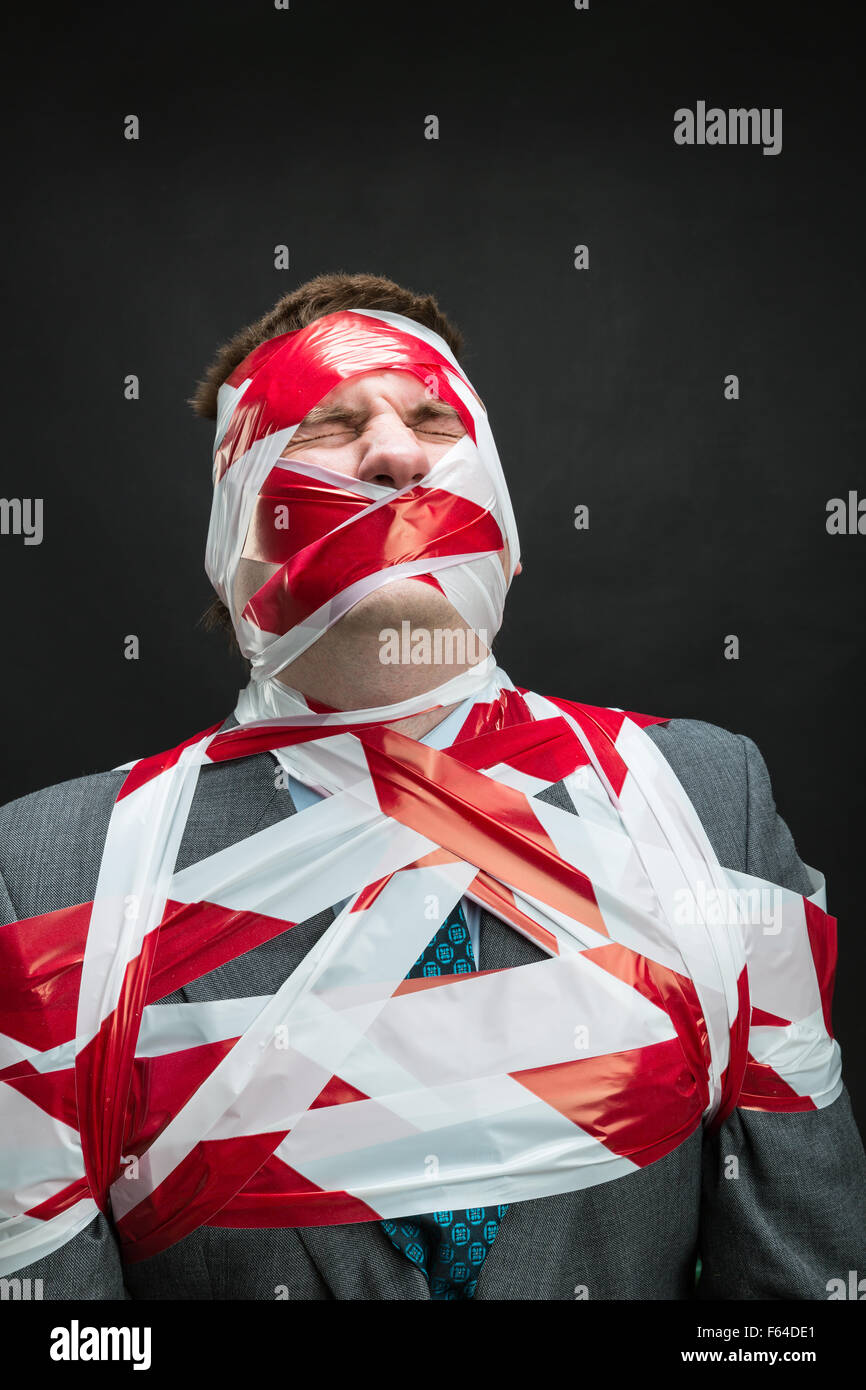 Victum man with stripped duct tape over body isolated on black - Stock Image