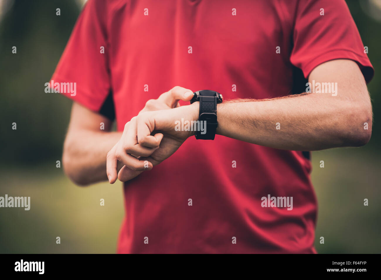 Runner using heart rate monitor training running, smartwatch checking performance or GPS. Man athlete looking at - Stock Image