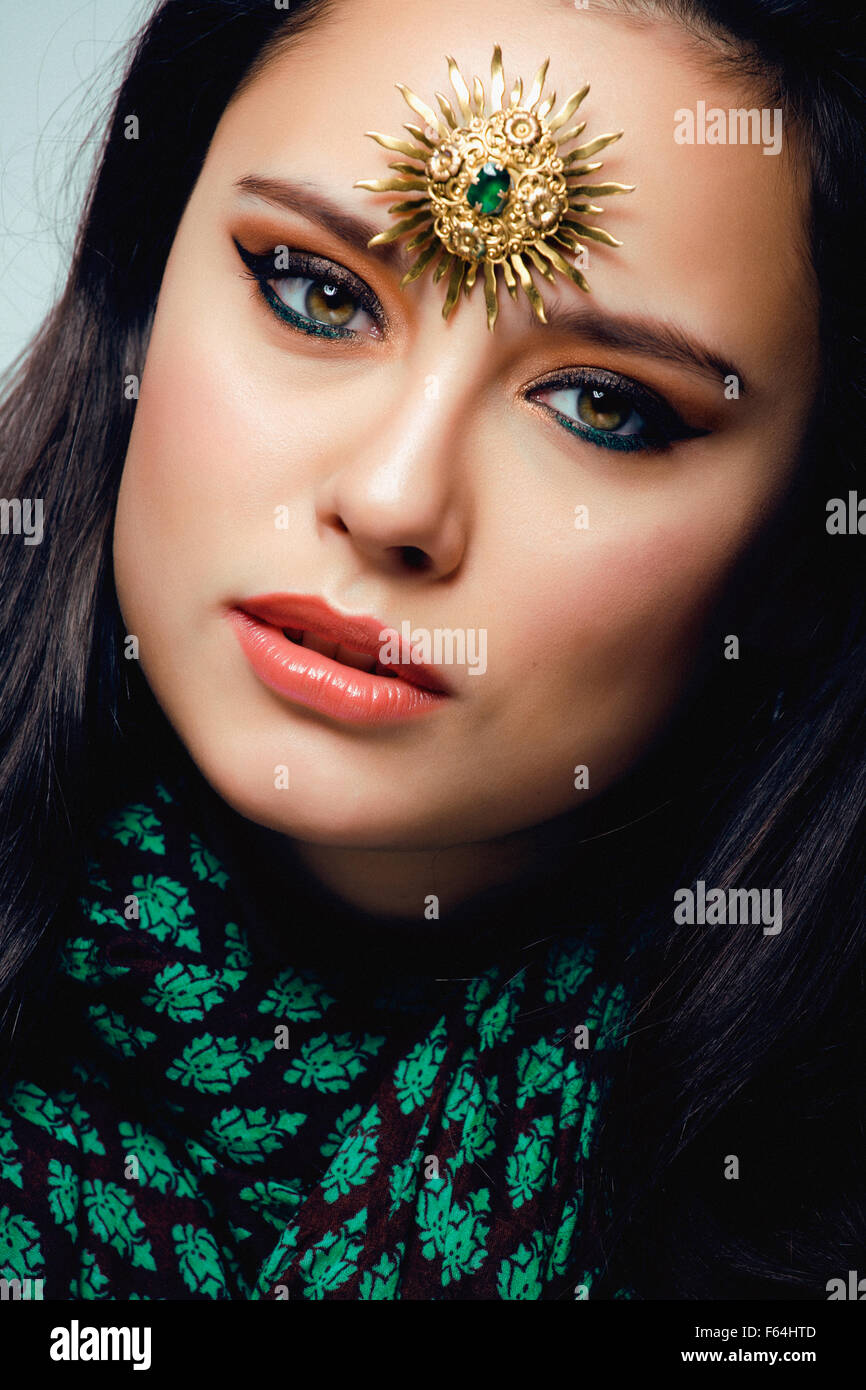 beauty eastern real woman with jewelry close up, bride star brooch green - Stock Image