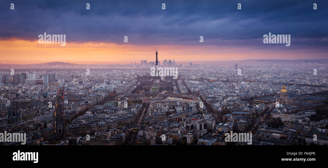 Panoramic aerial sunset view of Paris with the Eiffel Tower, La Defense and Invalides and storm clouds. France - Stock Image