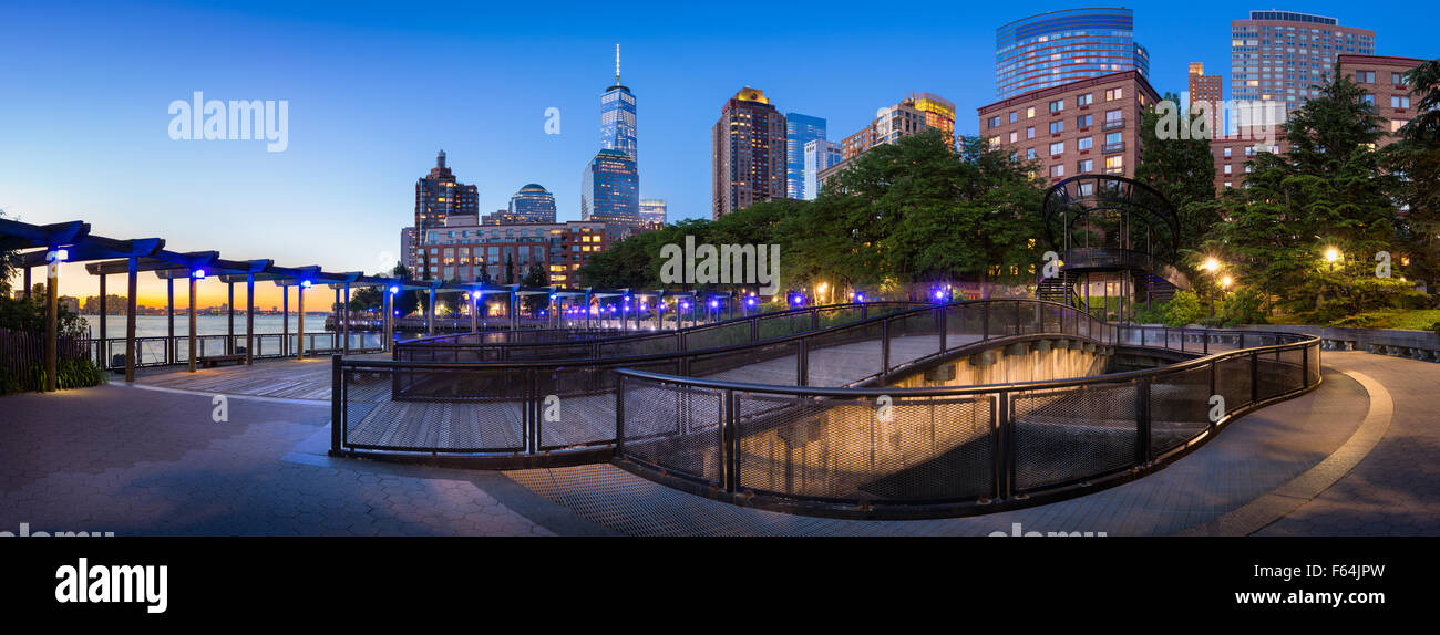 Hudson River Park with Manhattan Financial District skyscrapers. Sunset view of Lower Manhattan with One World Trade - Stock Image