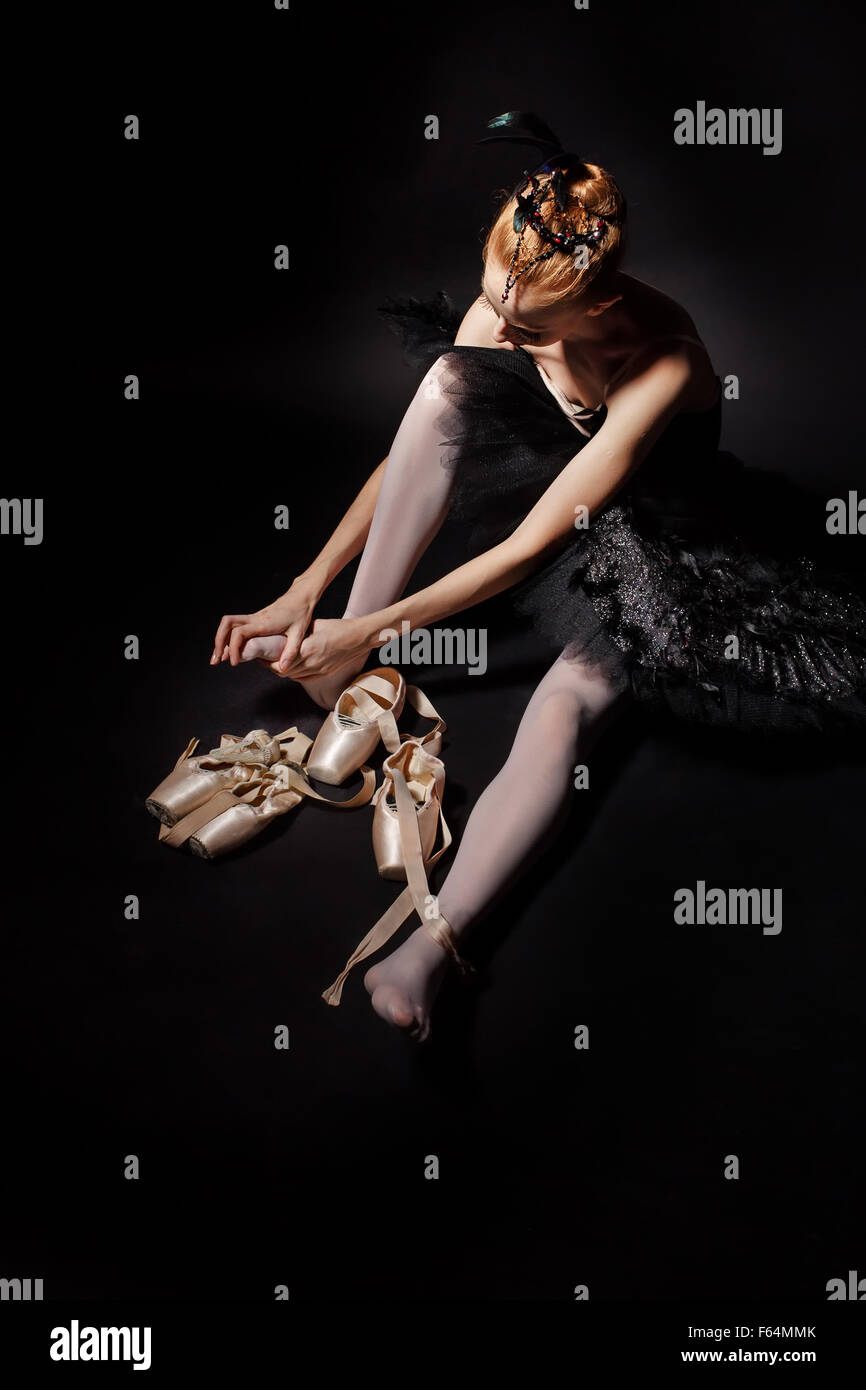 Slim ballerina in a black corset and black tutu tying pointe shoes. Classical Ballet. - Stock Image