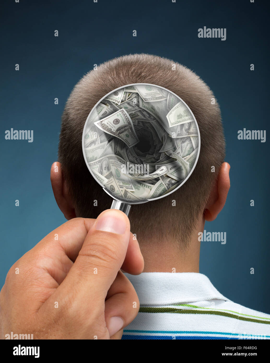 Looking to a mans head thinking about money through magnifying glass - Stock Image