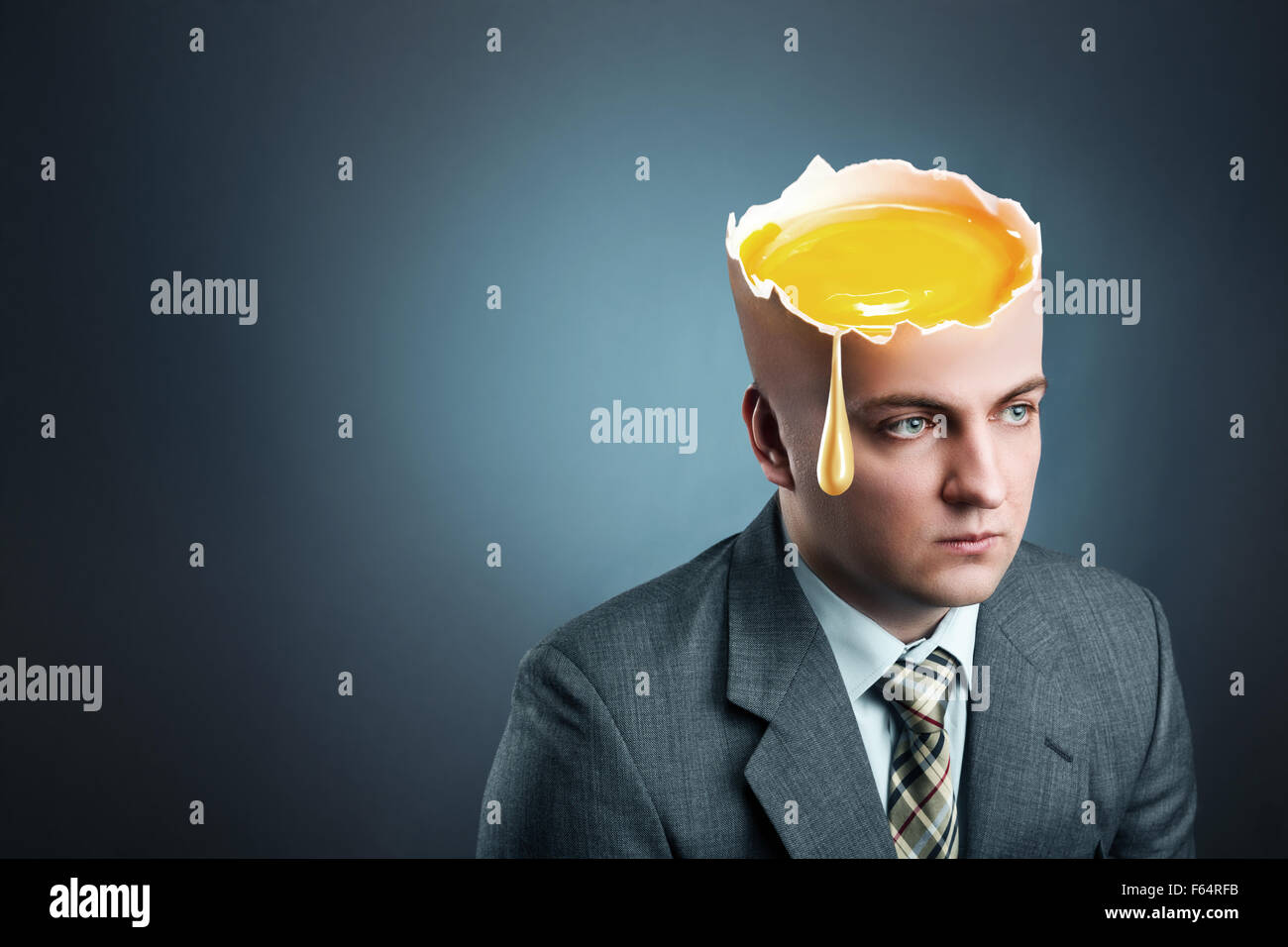 Sad businessman with egg head isolated on gray - Stock Image