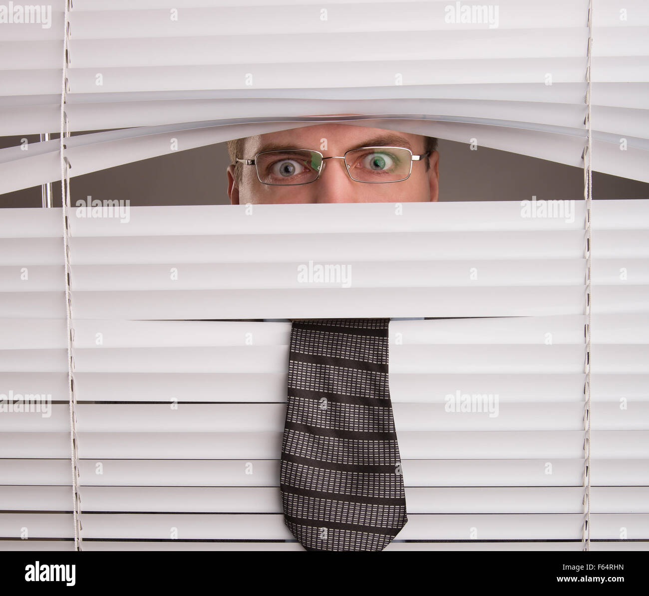 A young man looking through window blinds - Stock Image