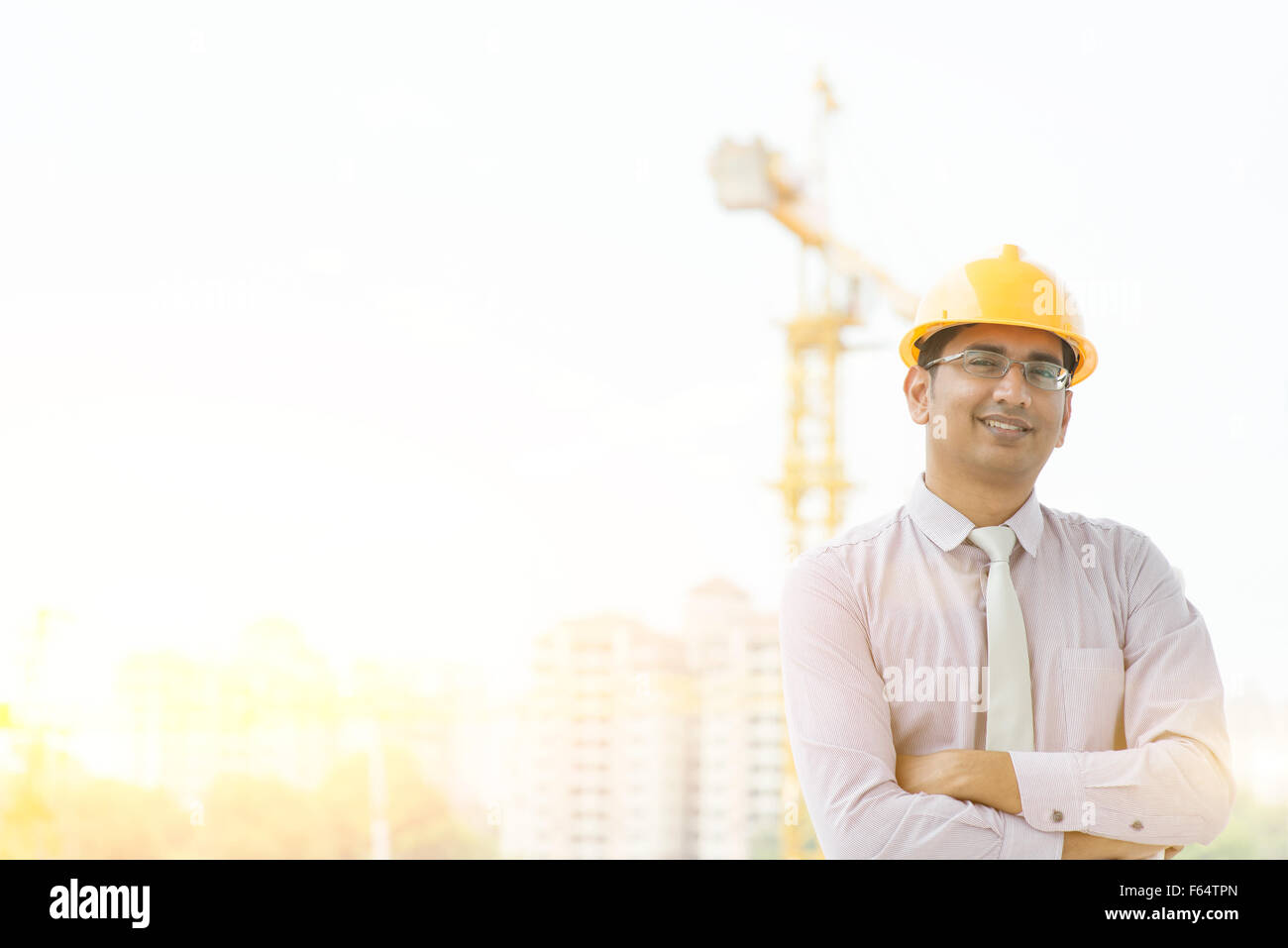 74dba5ab8bd Portrait of Asian Indian male site contractor engineer with hard hat  looking at camera and smiling at construction site