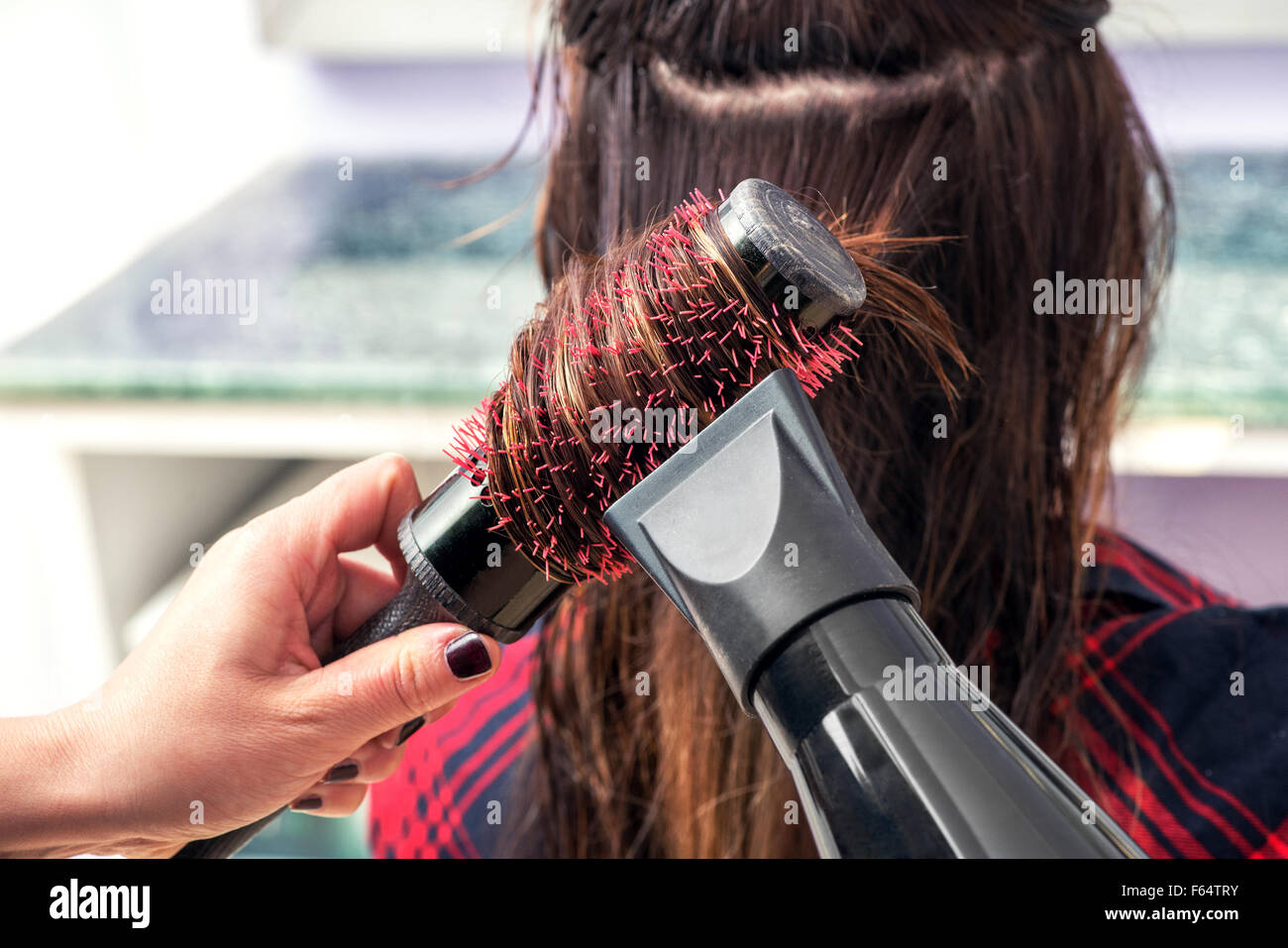 Hairstylist brushing the long brown hair of a woman in her hair salon - Stock Image