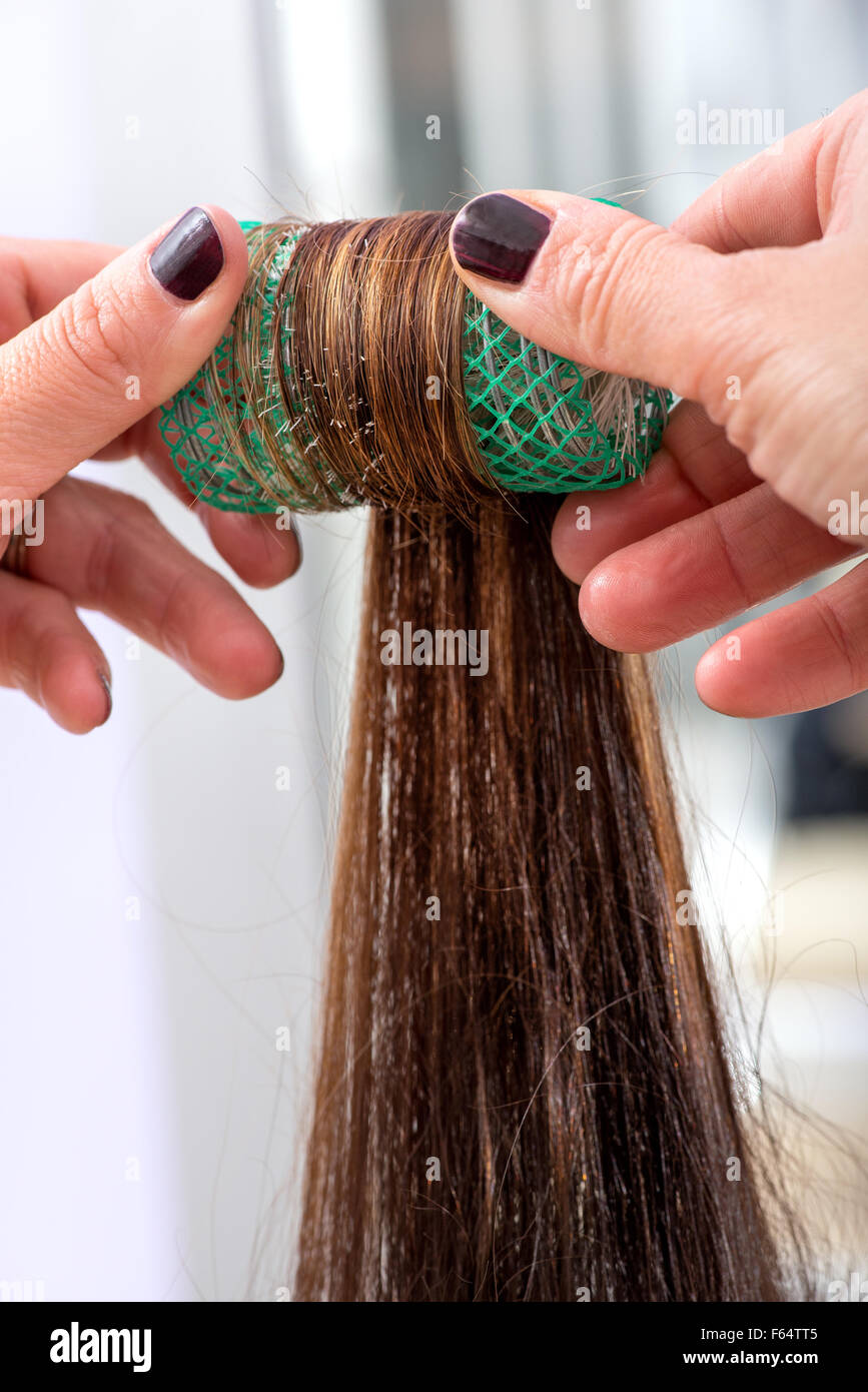 Hairdresser rolling a clients long brown hair on a roller or hair curler as she styles it in a salon - Stock Image