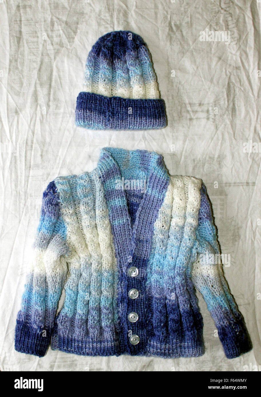 Hand knitted by Carole a babies cardigan and hat set, created from acrylic yarn in blue and white shades. - Stock Image