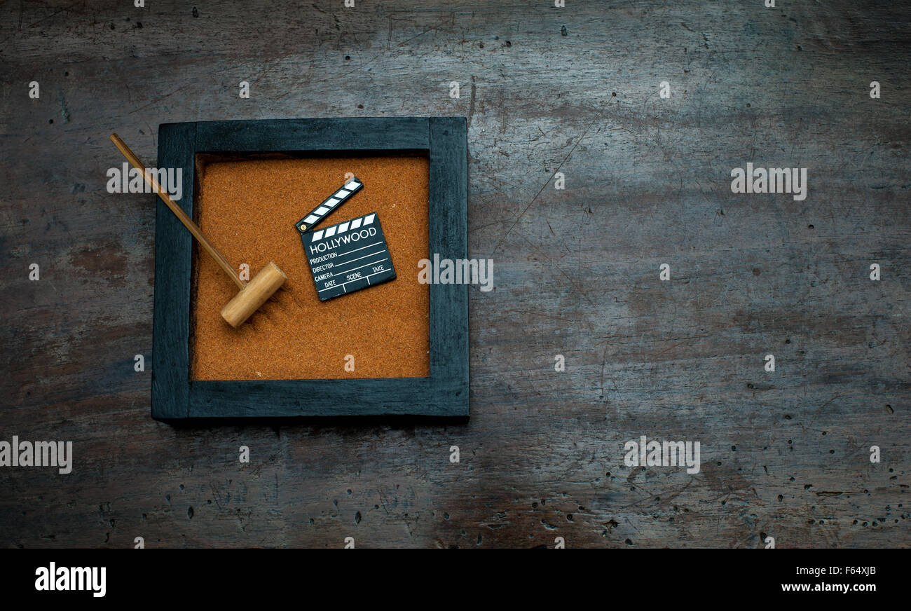 Zen garden with rake and movie clapper board, orange sand on aged scraped wood - Stock Image