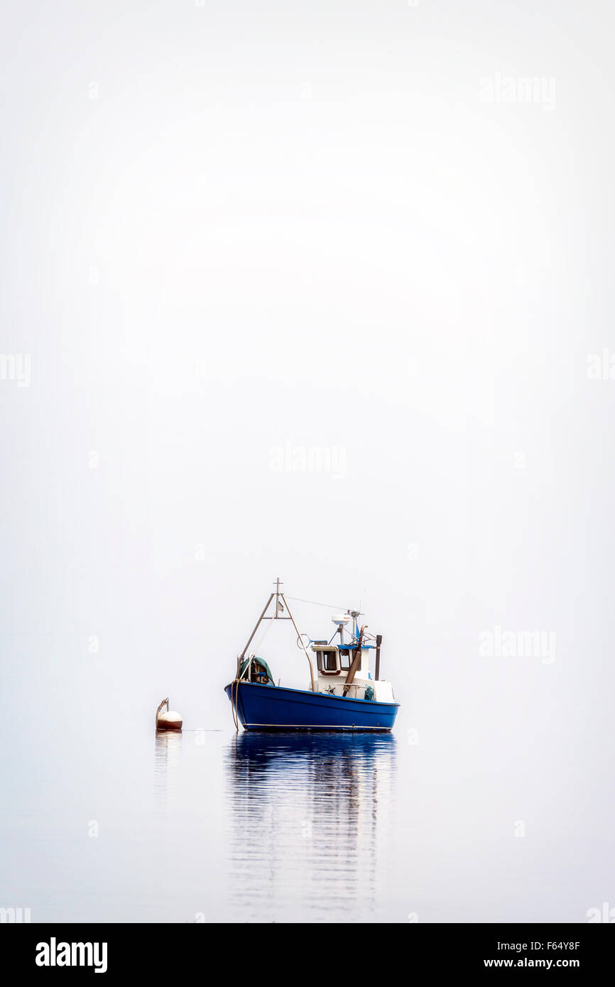 a fishing boat on a misty sea Stock Photo
