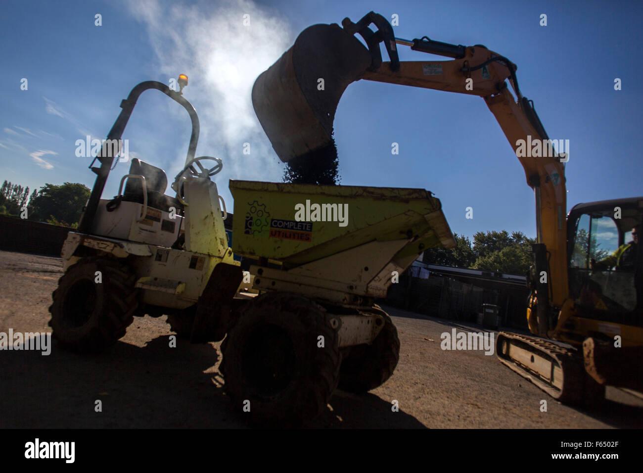 a digger puts hot asphalt into a dump truck - Stock Image