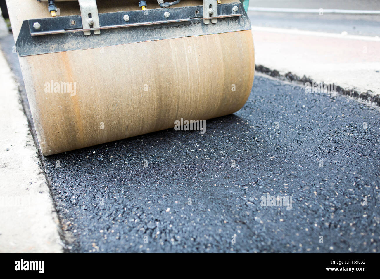 a roller flattens asphalt into a trench on a road - Stock Image