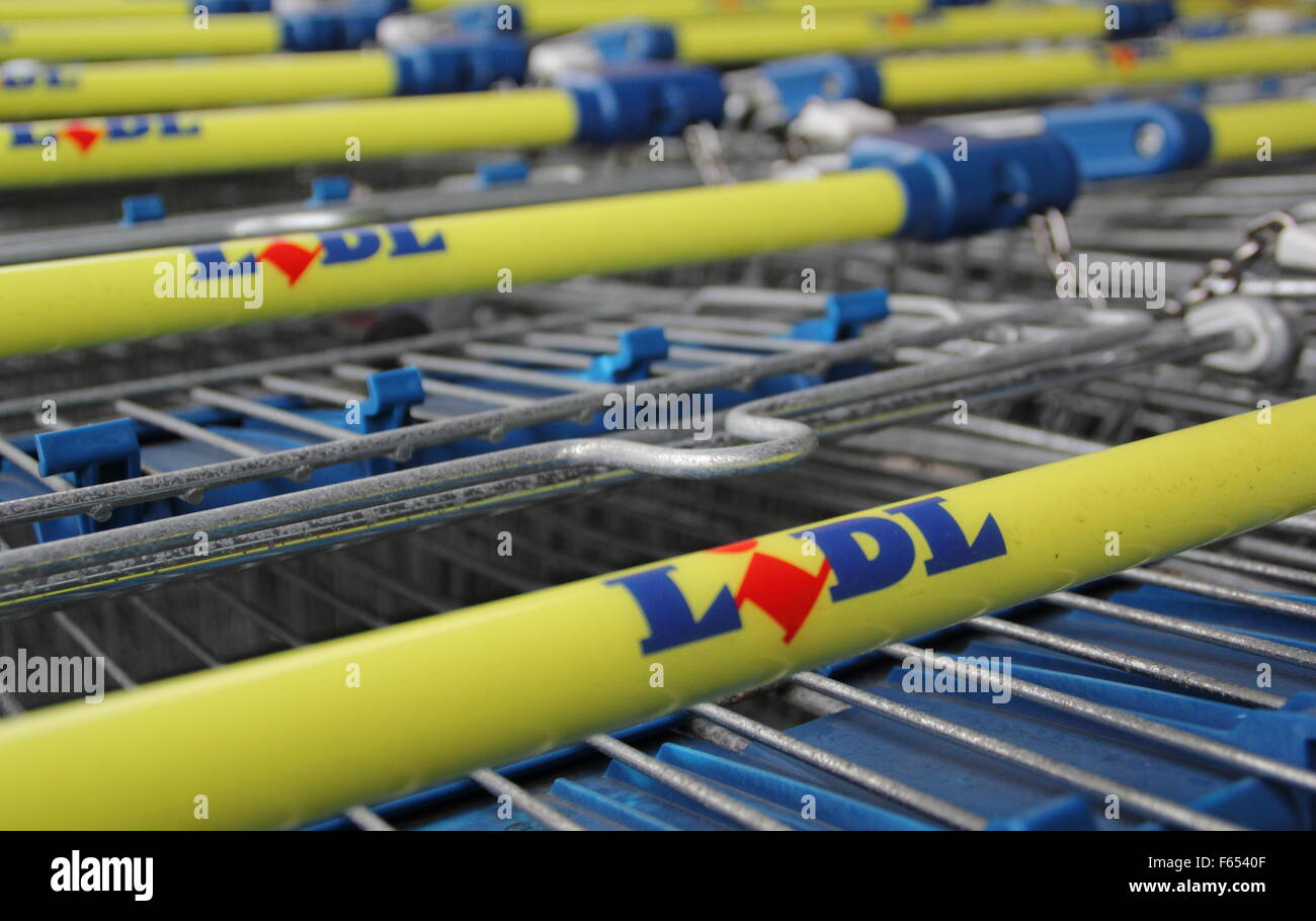 Lidl supermarket trolleys  lined up and cchained together outside a store in England UK - Stock Image