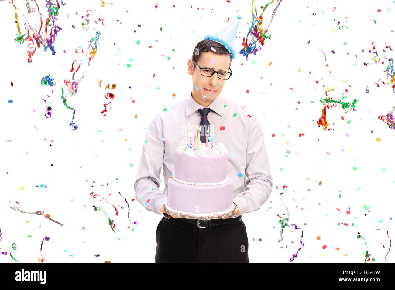 Sad young man holding a birthday cake and crying with confetti streamers flying around him isolated on white background - Stock Image
