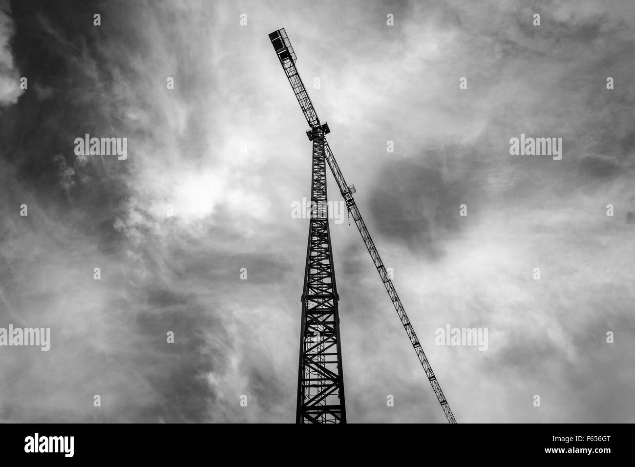 Construction Crane Under A Cloudy Sky In Black And White