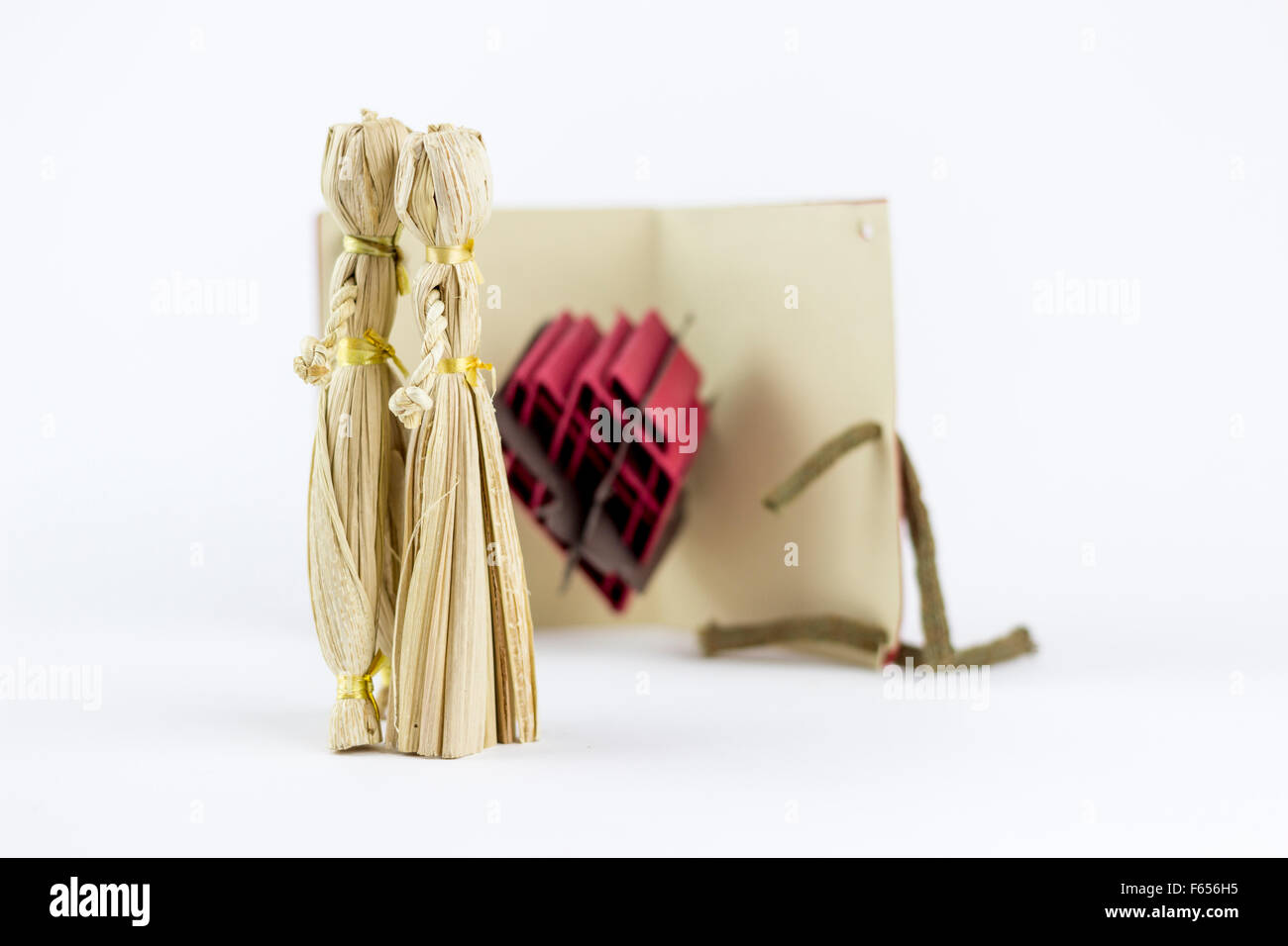 Two straw figurines, kissing in front of a love letter,  on a white background - Stock Image