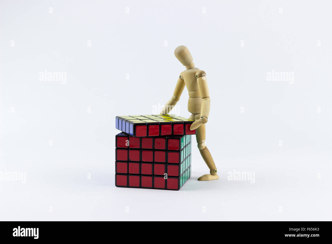 Wooden puppet trying to solve a puzzle cube, on a white background - Stock Image