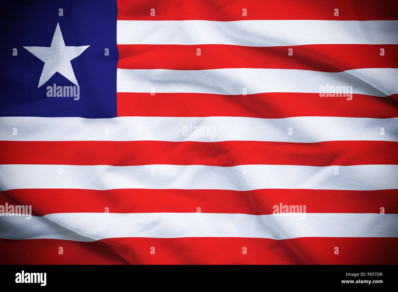 Wavy and rippled national flag of Liberia background. - Stock Image