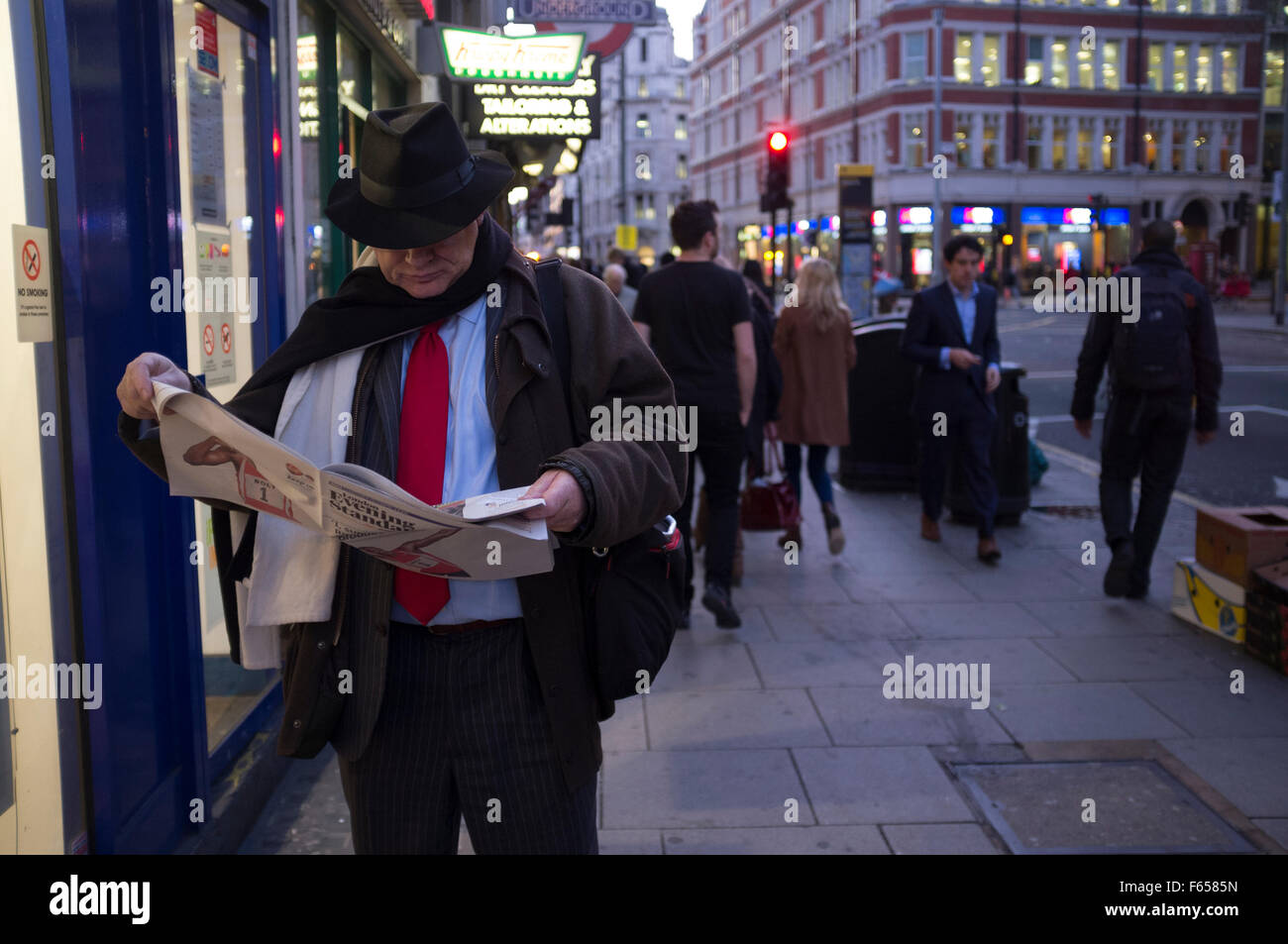 A city gent engrossed in the Evening Standard newspaper on a London street early evening - Stock Image