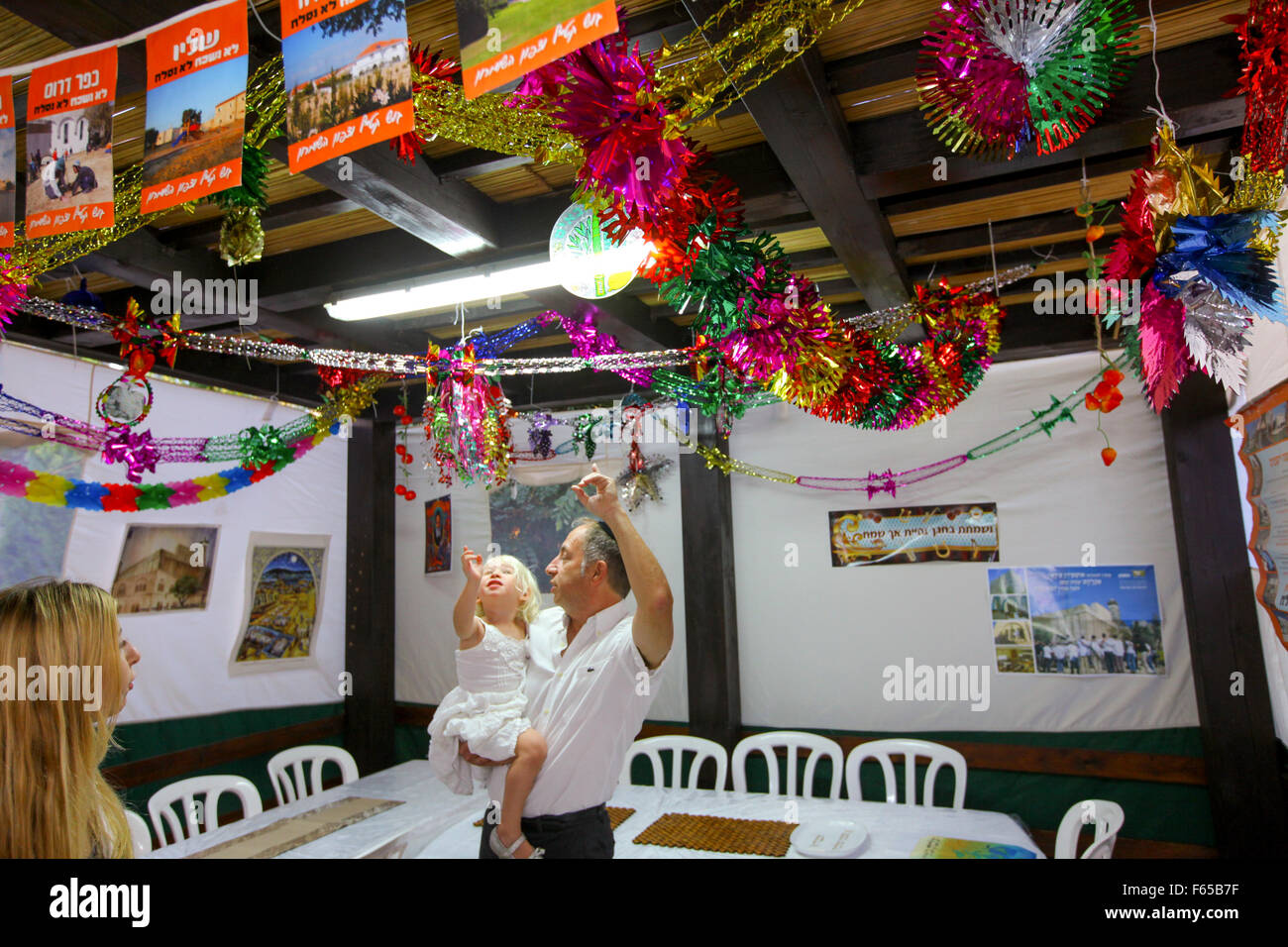 A family inside a decorated Sukkah - Stock Image