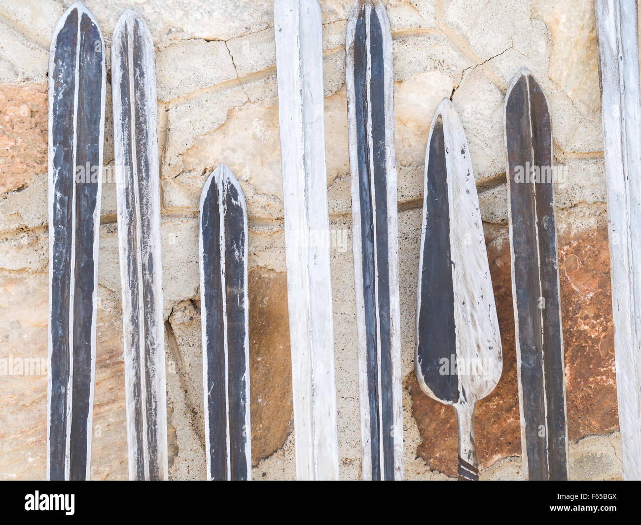 Maasai weapons: swords, spears and knifes, sold as souvenirs at a local Maasai market. - Stock Image