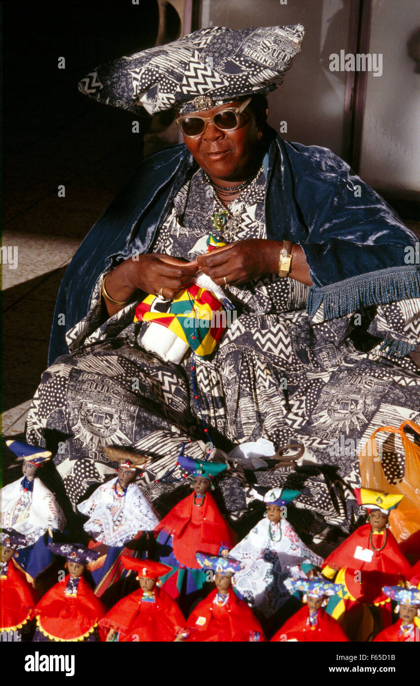 Herero woman wearing traditional dress sitting with hand made dolls, Namibia Stock Photo