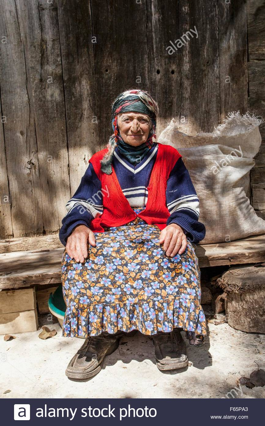 This old woman is a member of the ethic minority Hemsinli family and is sitting in her rural yard in Kayagantas, - Stock Image