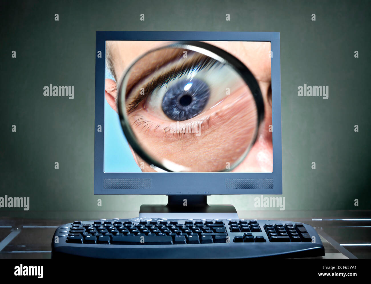 Eye with magnifier on a computer screen as an icon for monitoring - Stock Image