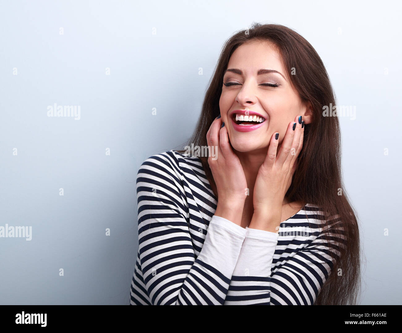 Happy loudly laughing woman holding hands the face on blue background - Stock Image