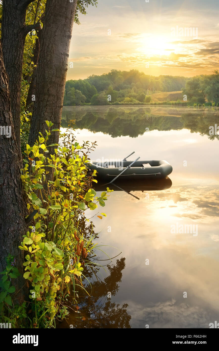 Inflatable boat on river at the sunrise - Stock Image