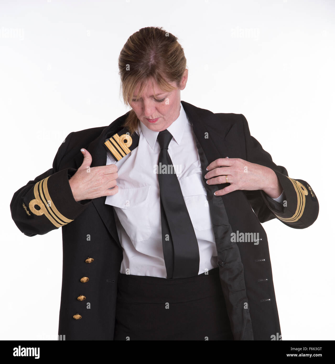 Lt Commander female South African naval officer getting dressed into uniform jacket - Stock Image