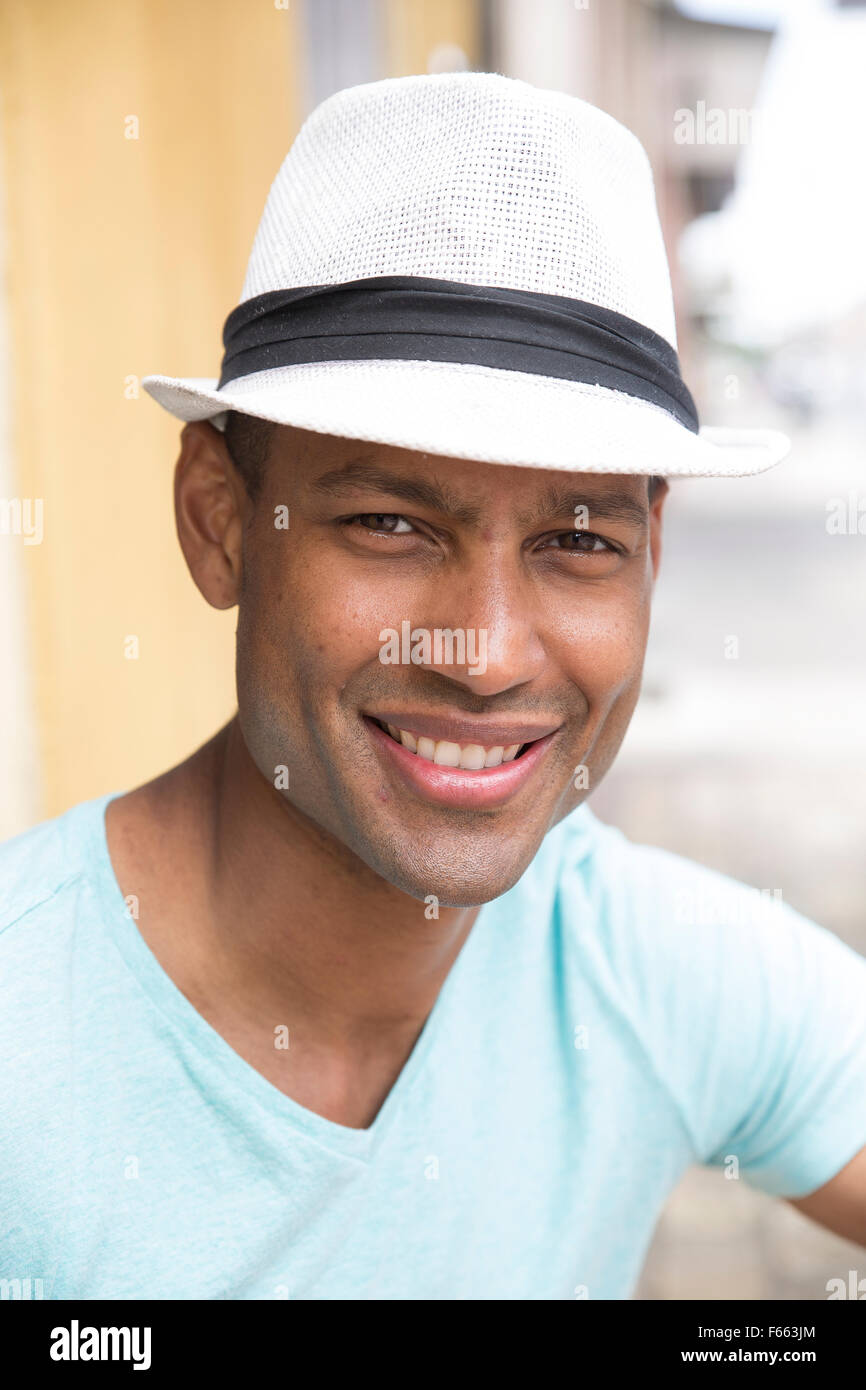 Head shot of any ethnic man smiling wearing a light blue green t-shirt and black and white fedora - Stock Image