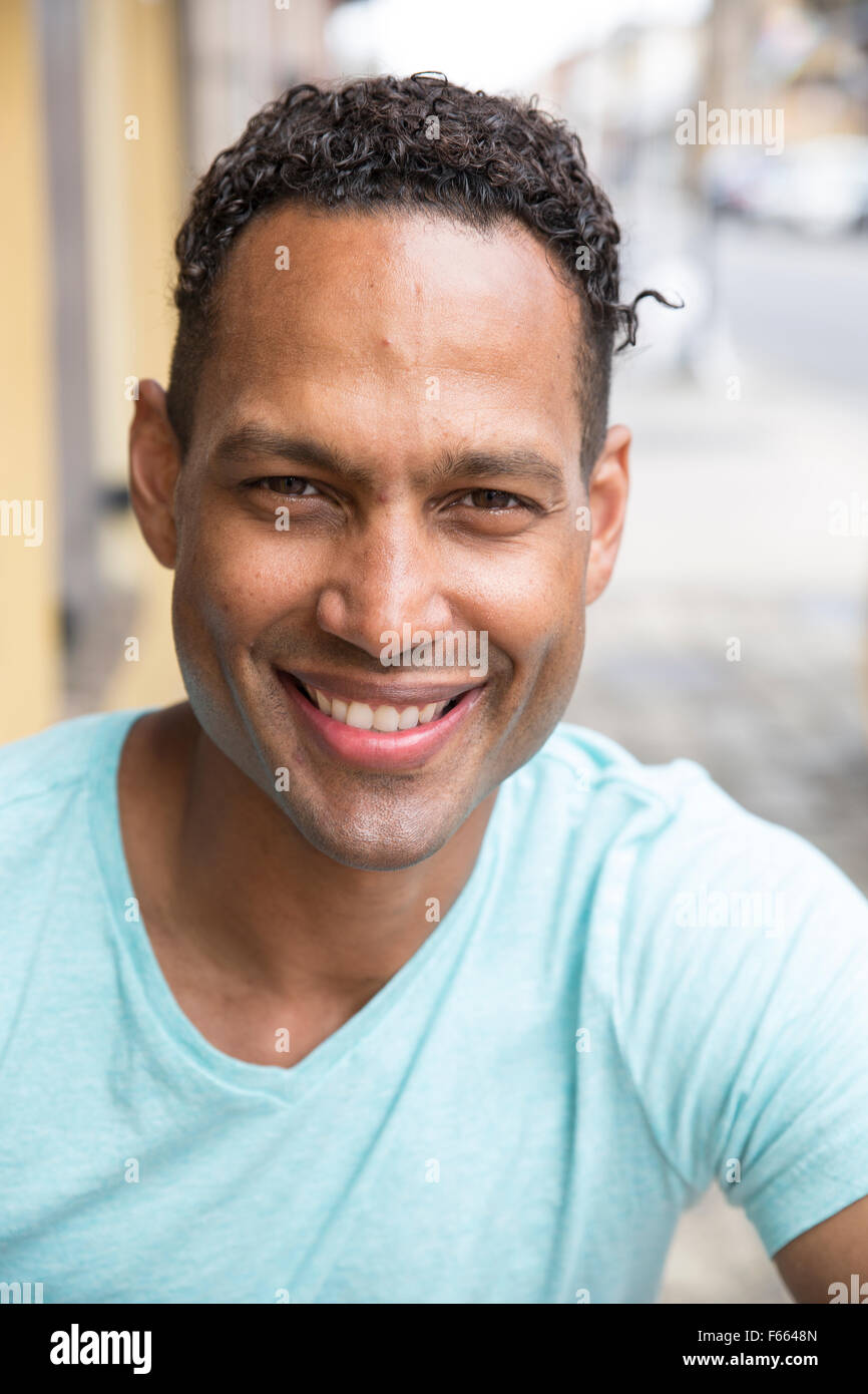 Head shot of any ethnic man smiling wearing a light blue green t-shirt. - Stock Image